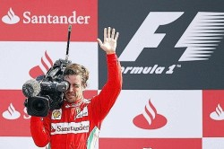 Ferrari Formula One driver Alonso of Spain waves as he films supporters from the podium as he celebrates his third place in the Italian F1 Grand Prix at the Monza circuit