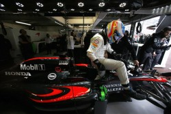 Fernando Alonso climbs from his car in the garage.